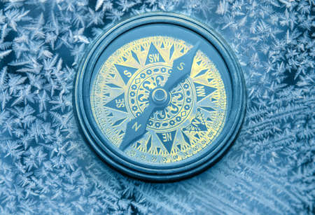azimuth: Vintage compass on snowflakes in blue toning
