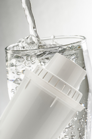 purify: New water filter tube with glass on white background Stock Photo