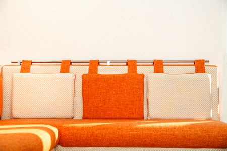 Cosy orange and white sofa with pillows photo