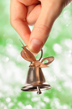woman hanging toy: Bell in female hand closeup on sparkle background