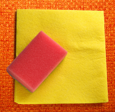 orange washcloth: Yellow duster and red sponge in closeup