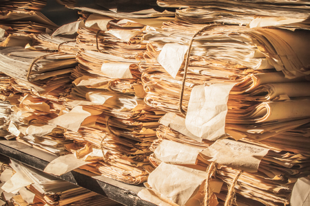 old office: Paper documents stacked in archive in closeup