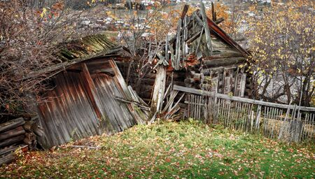 Old ruined village wooden house in autumn photo