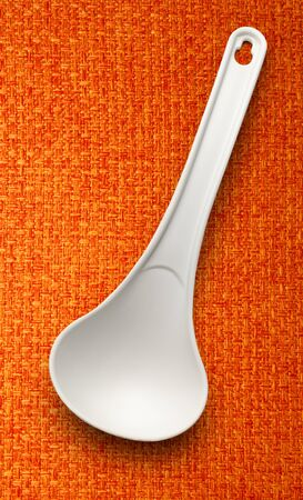 ladle: White plastic ladle on the cloth background