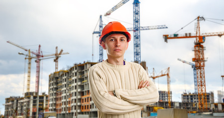 Workman in red helmet on background of buildings under construction and cranes photo