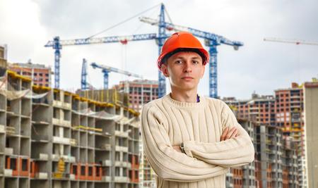 casco rojo: Trabajador en casco rojo sobre fondo de edificios en construcci�n y gr�as Foto de archivo