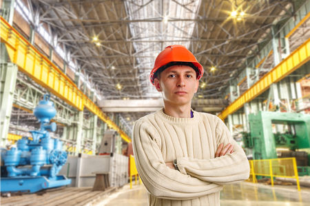 Workman in red helmet in the workshop of machinery plant photo