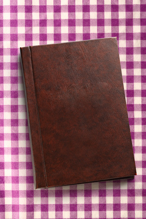 lila: Blank closed notebook on checked lila background