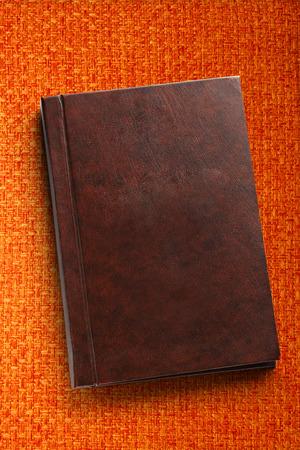 Blank closed notebook on orange fabric background photo