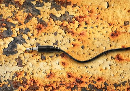 rusty background: Black jack plug on the rusty background