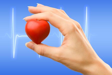 símbolo de la medicina: Mano femenina con el coraz�n rojo que sostiene con cuidado