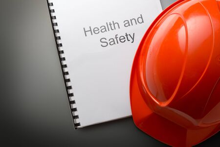 work safety: Health and safety register with helmet in closeup Stock Photo