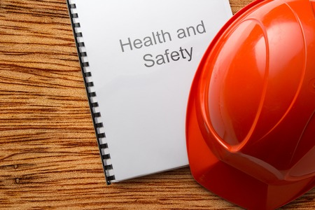 work material: Health and safety register with helmet in closeup Stock Photo