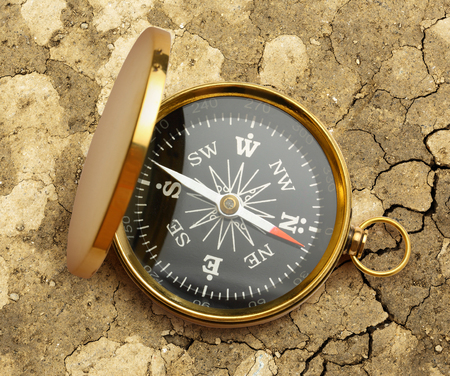 Golden vintage compass opened on soil background
