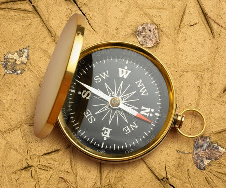 magnetic stones: Golden vintage compass opened on soil background