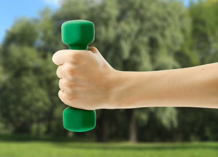 Female hand holding green dumbbell in closeup Stock Photo
