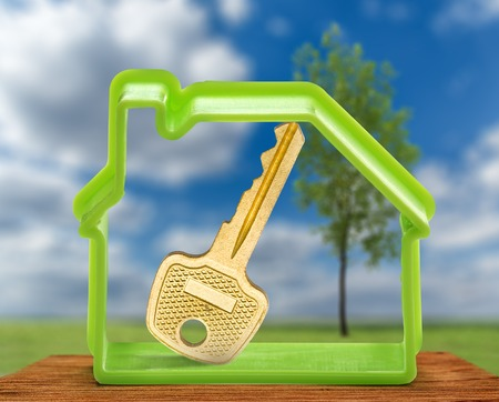 golden key: Toy house form with key as symbol outdoors Stock Photo