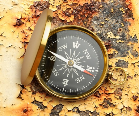 rusty background: Golden vintage compass opened on rusty background