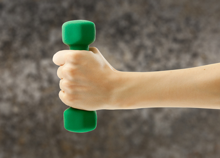strong women: Female hand holding green dumbbell in closeup Stock Photo