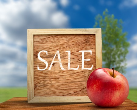 Red apple with wooden frame on nature background