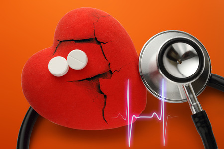 small group of objects: Heart, stethoscope and pills on red background