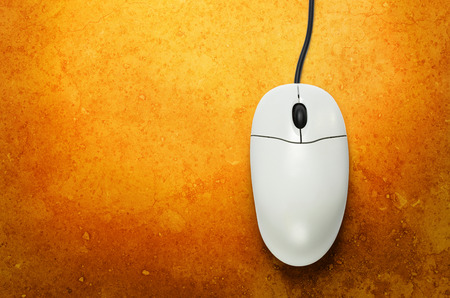 scrollwheel: Computer mouse on yellow background  in closeup