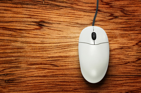 scrollwheel: Computer mouse on wooden background  in closeup