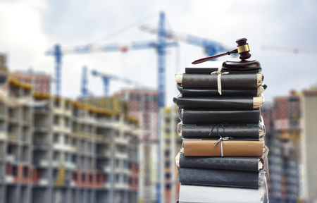 Document files with gavel on buildings under construction