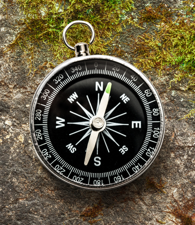 magnetic stones: New black compass on moss in closeup