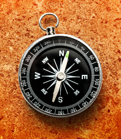 New black compass on orange in closeup Stock Photo