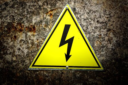 old sign: Old yellow sign with high voltage icon Stock Photo