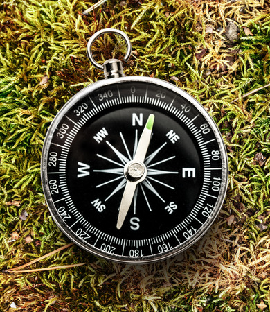 magnetic stones: New black compass on grass in closeup