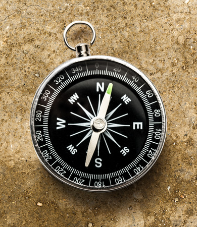 New black compass on soil in closeup Stock Photo