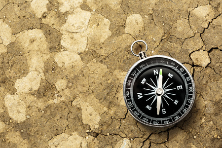 Black compass on the dry soil background