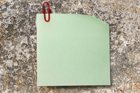 Blank green sticker and red clip on stone surface photo