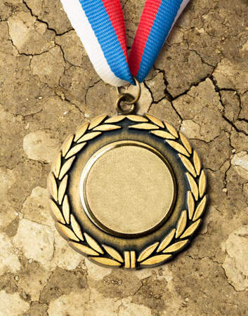 red competition: Metal medal with tricolor ribbon on dry soil