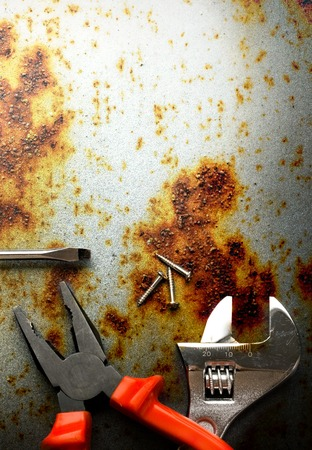 rusty background: Pliers, screwdriver and spanner on rusty background Stock Photo