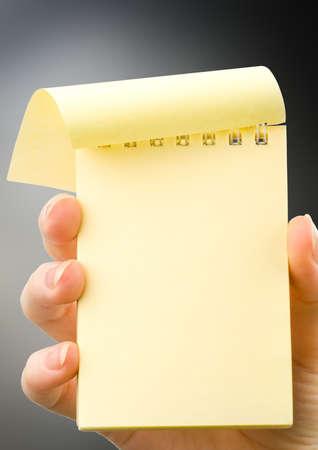 papel de notas: Mano femenina que sostiene la libreta en blanco verde vertical