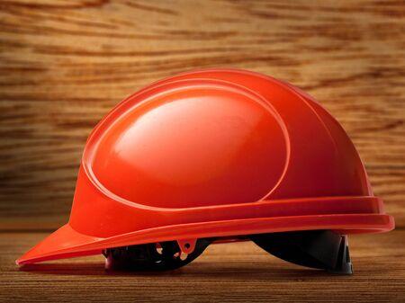 casco rojo: casco rojo sobre fondo de madera en primer