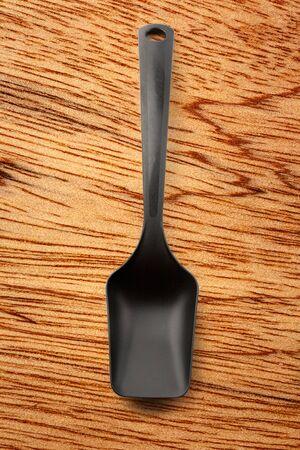 heatproof: Black plastic kitchen spoon vertical in closeup Stock Photo