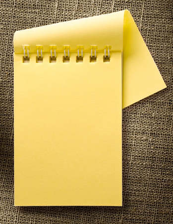 yellow notepad: Blank yellow notepad on sack background open Stock Photo