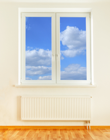 torridity: Radiator and window in home interior with blue sky view