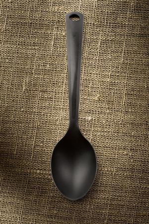 heatproof: Black plastic spoon on sack background vertical Stock Photo