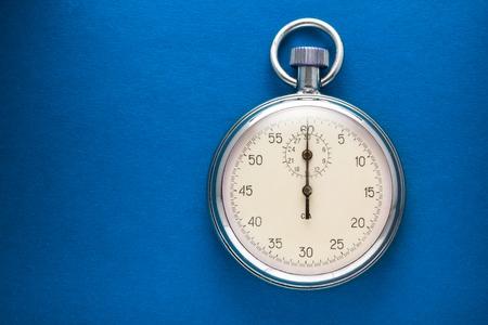 Single stopwatch closeup on blue paper background