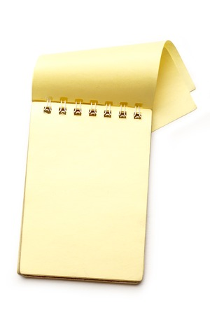 small paper: Yellow blank notepad with open page closeup