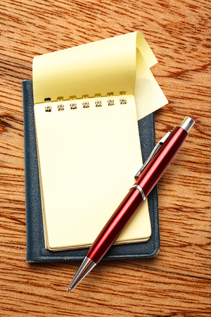 red pen: Yellow blank notepad open with red pen Stock Photo