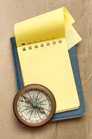 yellow notepad: Vintage compass and blank yellow notepad open
