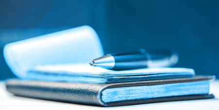 business book: Paper blocks with pen in blue toning