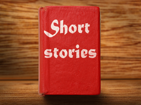 story: Old red short stories book on wooden background closeup Stock Photo