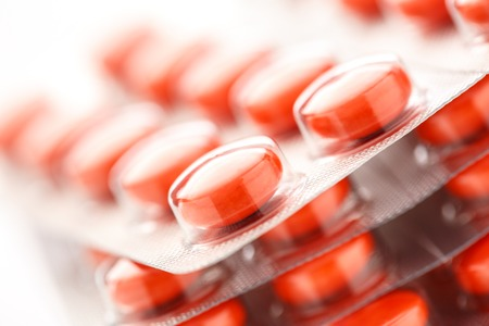 Red tablets in plastic packing as background Standard-Bild